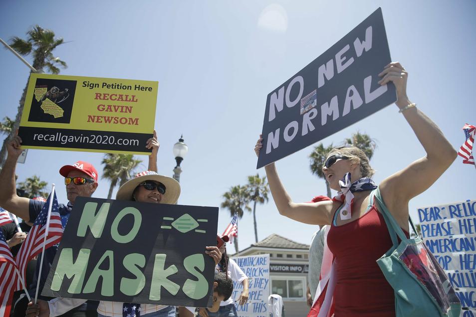 USA, Huntington Beach: Demonstranten protestieren gegen die Corona-Maßnahmen und das Tragen von Schutzmasken.