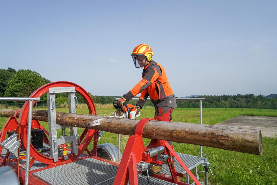 Mit einem Baumbiegesimulator können Feuerwehrleute das Sägen von umgeknickten Bäumen üben. Ausbilder Mathias Mitzscherling macht es vor.