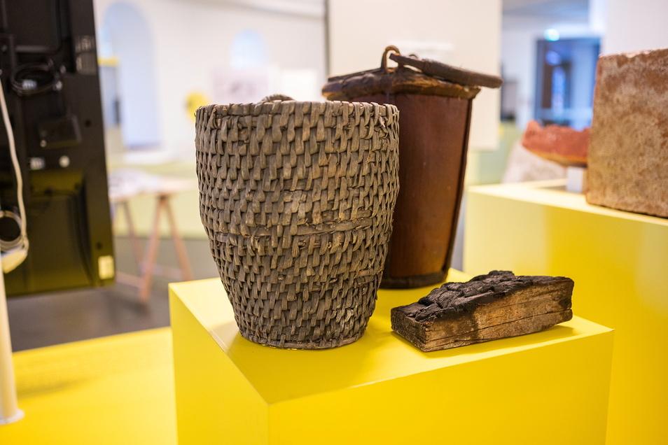 Zwei Löscheimer aus dem 18. und ein angekohltes Stück Holz aus dem 17. Jahrhundert erinnern an die großen Görlitzer Stadtbrände und an die Maßnahmen, die man dagegen ergriff.