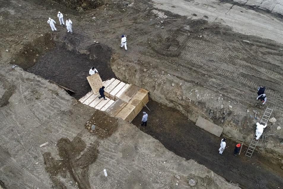 USA, New York: Arbeiter vergraben einfache Holzsärge in einem Graben auf Hart Island in der Bronx. Die Zahl der Corona-Toten in New York beträgt bereits mehr als 7000.