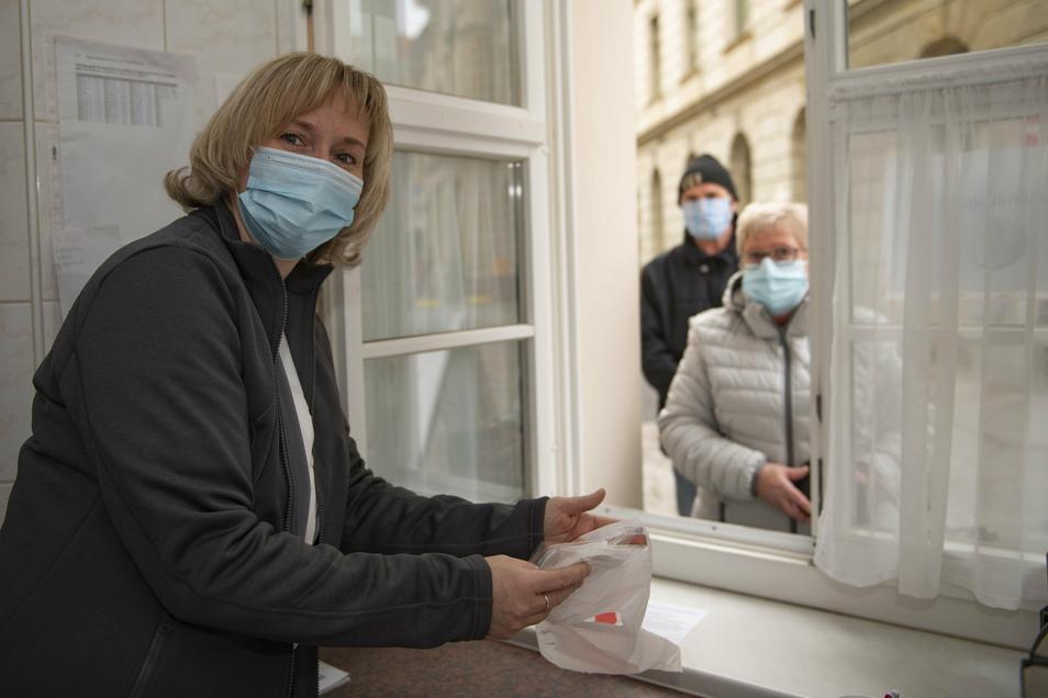 Ganztägig herrscht großer Andrang am Ausgabefenster der Großenhainer Löwen-Apotheke: Romy Mieth gibt kostenlos an bezugsberechtigte Kunden drei FFP2-Masken aus.
