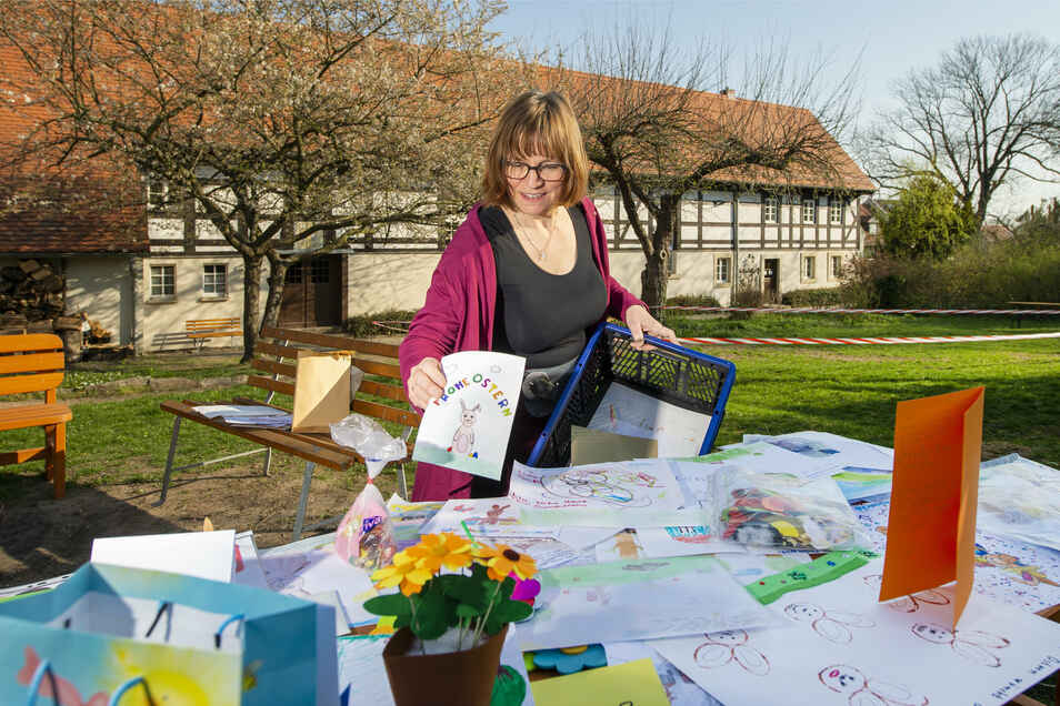 Frederike Knittel breitet auf einem Tisch im Garten des Pfarramtes in Reichenberg die Zeichnungen und Basteleien der Kinder aus.