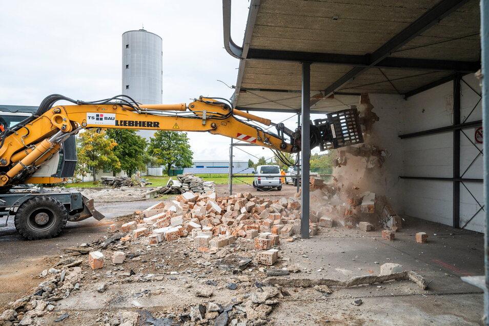 Ein Bagger von TS Bau greift zu und reißt die Innenwände der Garagenhalle ein.