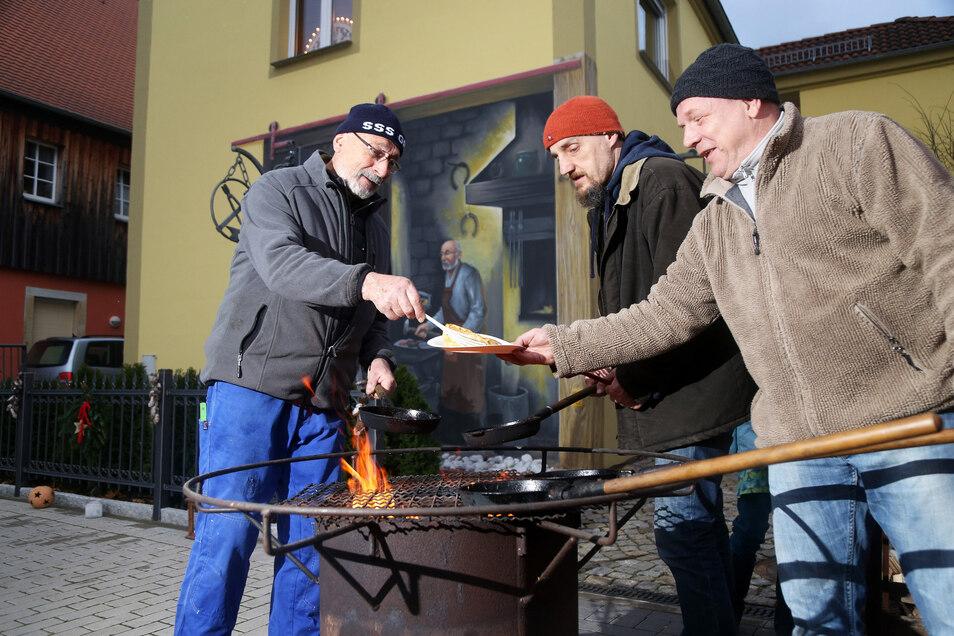 Schmied Werner Richter (links) und Michael Rudolph braten in Gröba leckere Plinsen über dem Holzfeuer.