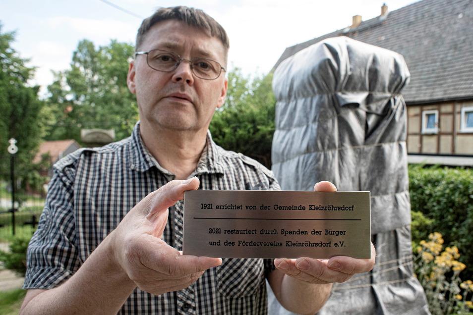 Ralf Granzow zeigt die Tafel, die dokumentiert, dass der Förderverein Kleinröhrsdorf das Kriegerdenkmal mit Spendengeldern restaurieren ließ.