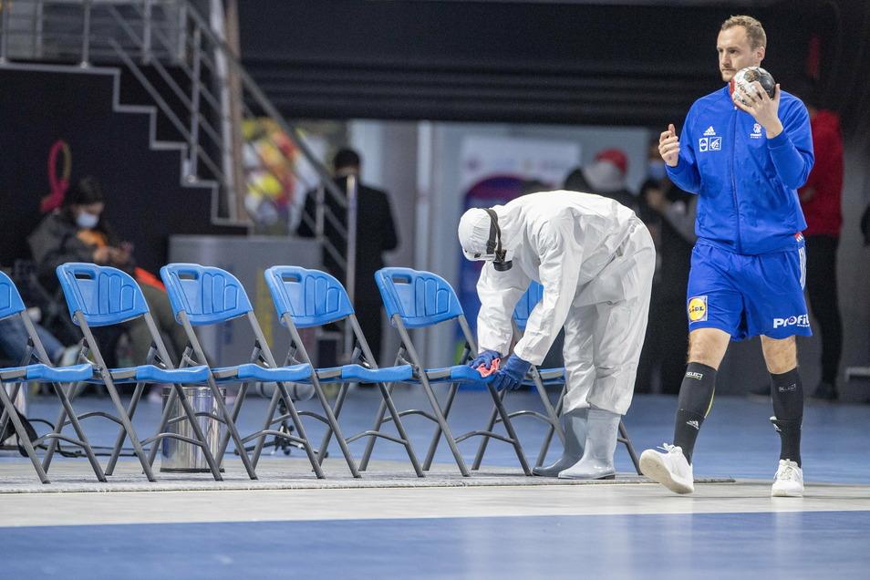 Ein Mitglied des Corona-Desinfektionsteams reinigt Stühle in Schutzkleidung.