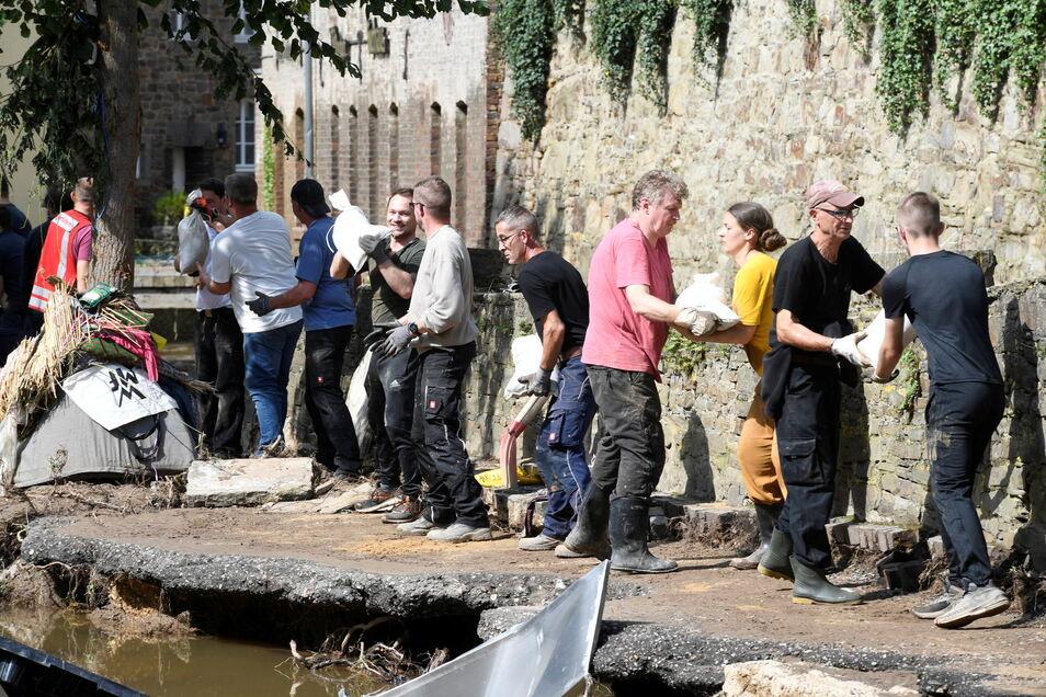 Mit einer Menschenkette befördern Helfer Sandsäcke in ein brüchiges Uferteil der Erft in Bad Münstereifel. In der Hochwasserkatastrophe haben sich die Menschen wieder mehr gegenseitig geholfen.