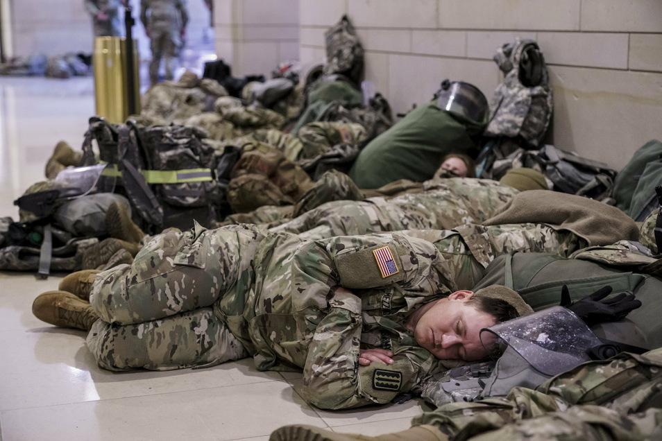 Ausruhen nach der Anreise: Mitglieder der Nationalgarde liegen in den Gängen des Kapitols. Die Soldaten sollen bis zur Amtsübergabe an den neu gewählten Präsidenten Joe Biden in Washington für Sicherheit sorgen.