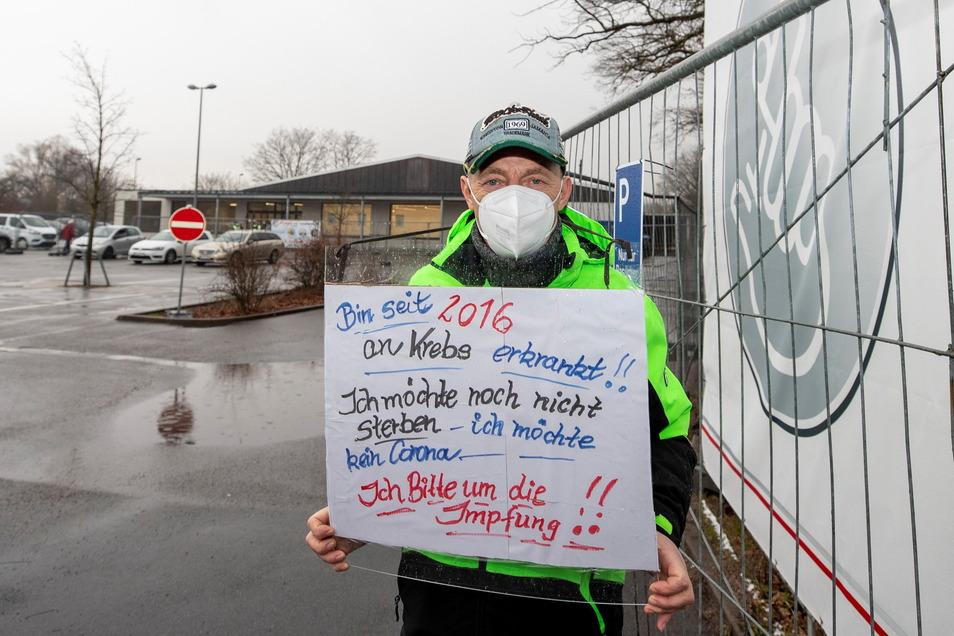 Ulf Buchholz aus Freital demonstriert mit einem Plakat vor dem Impfzentrum in Pirna.