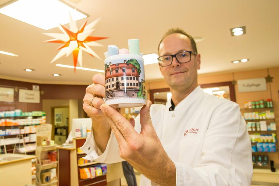 Apotheker Heiko Neumann präsentiert die neue Tasse für die jährliche Spendenaktion. Das wieder von Kümmel gestaltete Motiv zeigt diesmal die heutige Stadtbibliothek.