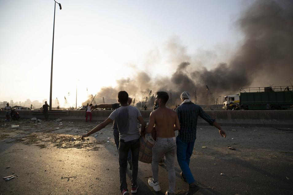 Menschen tragen in Beirut einen Verwundeten nach einer Explosion über eine Straße.