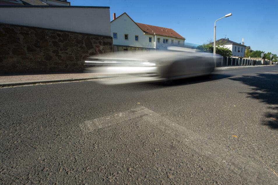 """Die Spuren einer weggefrästen Parkplatzmarkierung sind auf dem Asphalt der Borstraße noch deutlich zu sehen. Auf der gegenüberliegenden Straßenseite steht die ASB-Kita """"Rasselbande""""."""
