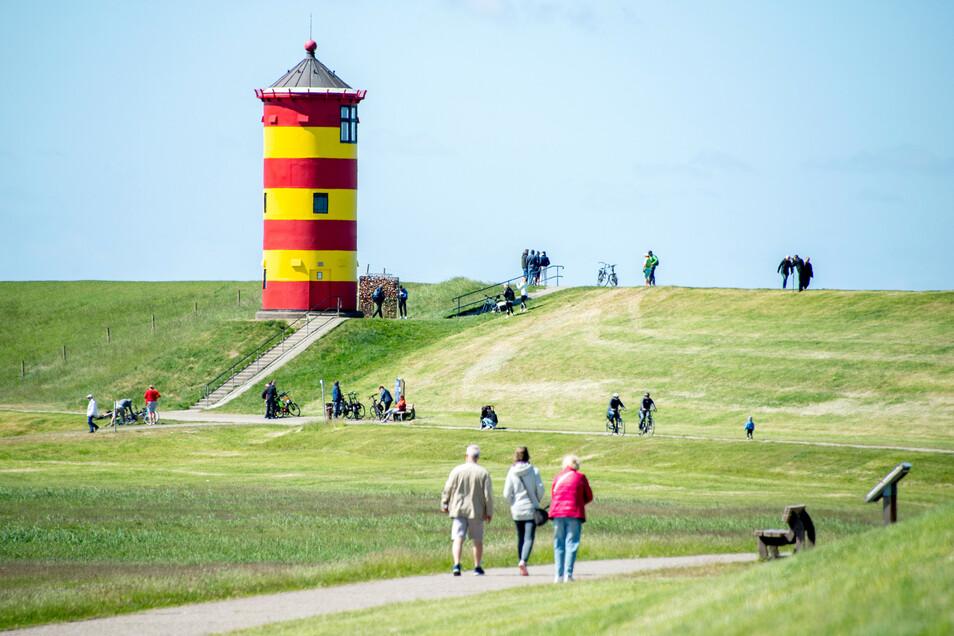 Touristen gehen auf dem Deich vor dem Pilsumer Leuchtturm in der Gemeinde Krummhörn spazieren. Der Turm mit einem rot-gelb gestreiften Anstrich diente als Kulisse für mehrere Spielfilme.