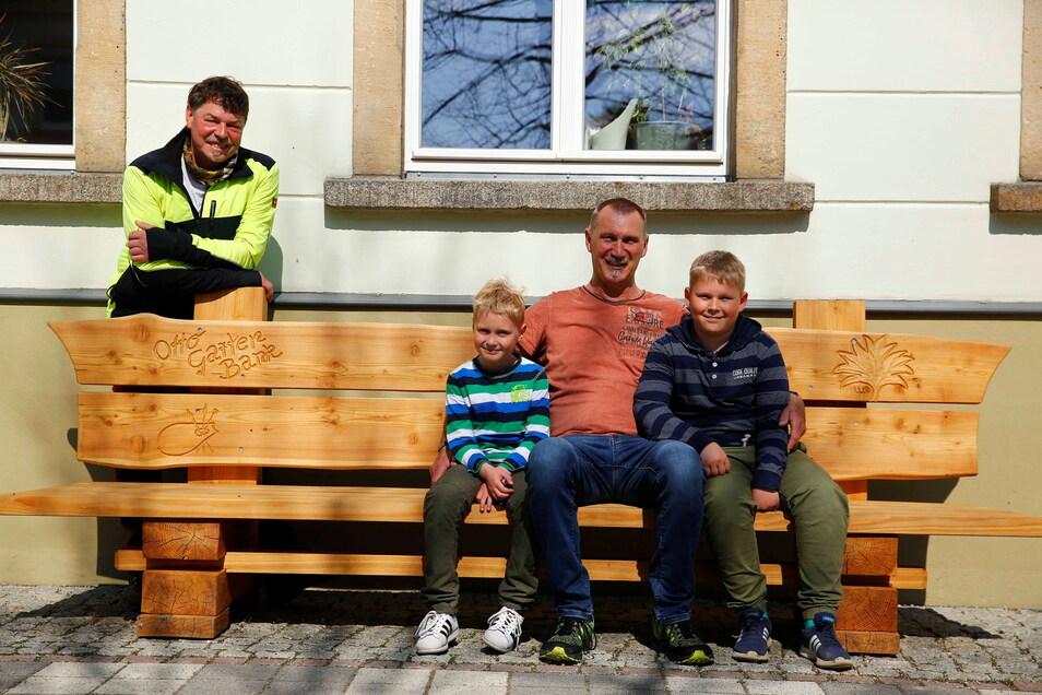 Sie haben schon mal auf der neuen Otto-Garten-Bank in Elstra Platz genommen: Sponsor Uwe König und seine beiden Enkel Levi (l.) und Luca. Im Hintergrund steht Holzkünstler Uwe Hohlefeld, der die Bank geschaffen hat.