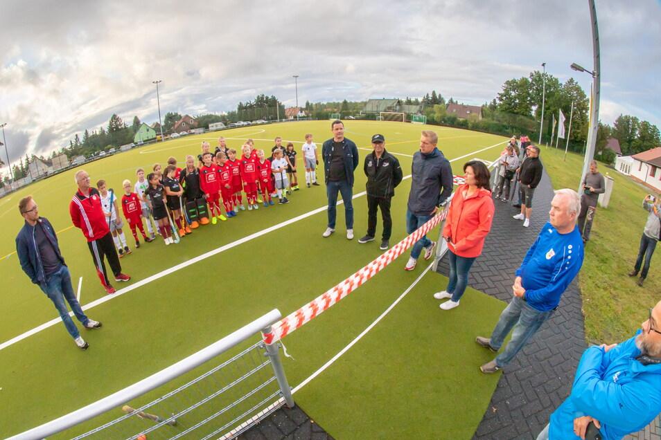 Im Beisein von Oberbürgermeisterin Beate Hoffmann (rote Jacke) wurde Freitagabend der neue Kunstrasenplatz in der Fichtestraße offiziell eingeweiht.