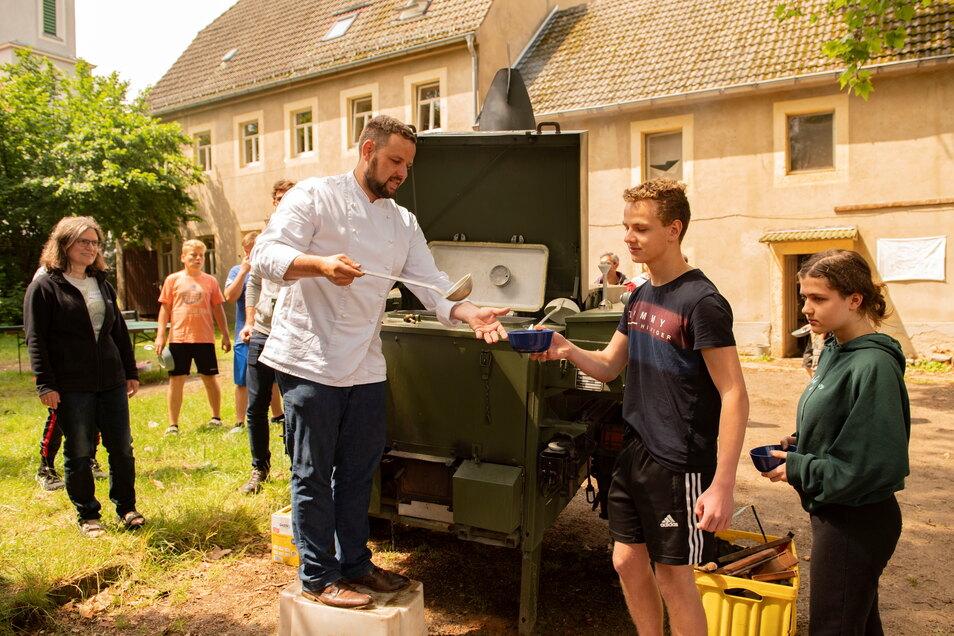 Sebastian Fischer bekochte die Konfirmanden im Camp auf dem Pfarrhof Skassa mit der Gulaschkanone. Auch Elia und Silvie lassen sich die Kartoffelsuppe schmecken.
