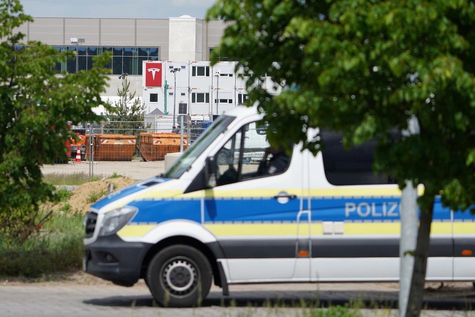 Ein Polizeiauto steht in Sichtweite der Tesla-Baustelle in Grünheide. Ganz in der Nähe haben vergangene Nacht Starkstromkabel gebrannt.