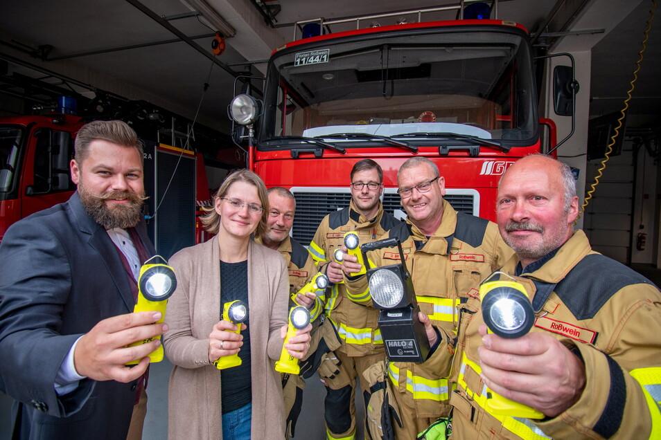 Katrin Stenker, Vorsitzende des SPD-Ortsvereins Roßwein, und Robert Heidrich, Leiter der Filiale Roßwein der Kreissparkasse Döbeln, haben die neuen LED-Lampen an die Kameraden der Ortsfeuerwehr übergeben.