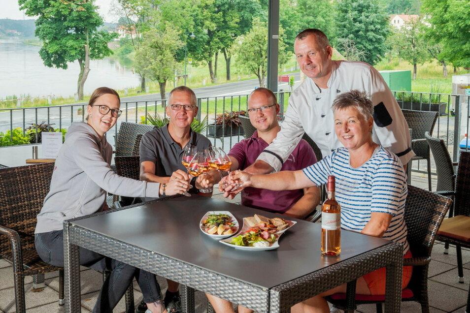 Familie Ulrich und ihr Koch Karsten Simon stoßen auf den Neubeginn an.