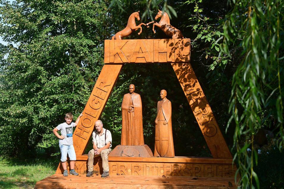 Günter Schönfelder mit Enkel Joshua am geschnitzten Denkmal für die Gebrüder Kahl und ihre Oybiner Ritterfestspiele.