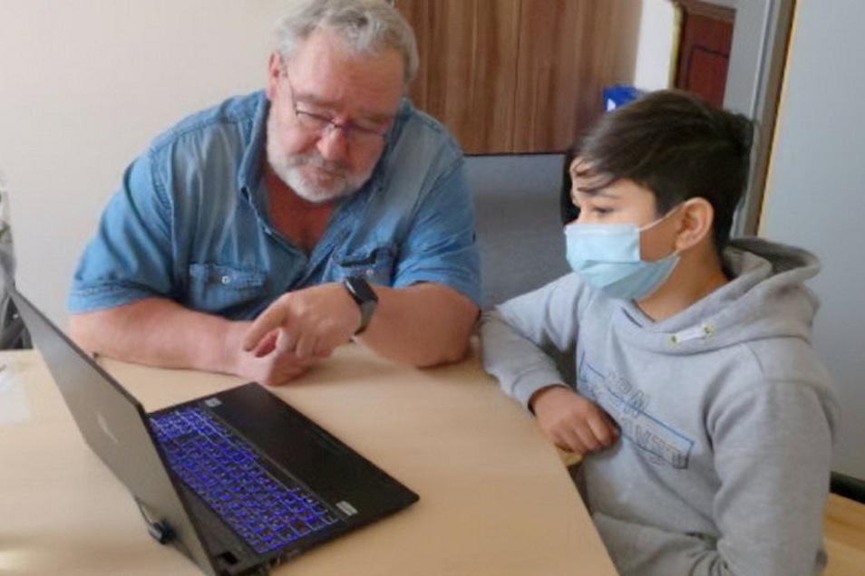 Thomas Winter, Schulleiter der Geschwister-Scholl-Oberschule Roßwein, erklärt einem Schüler die Handhabung des Notebooks.