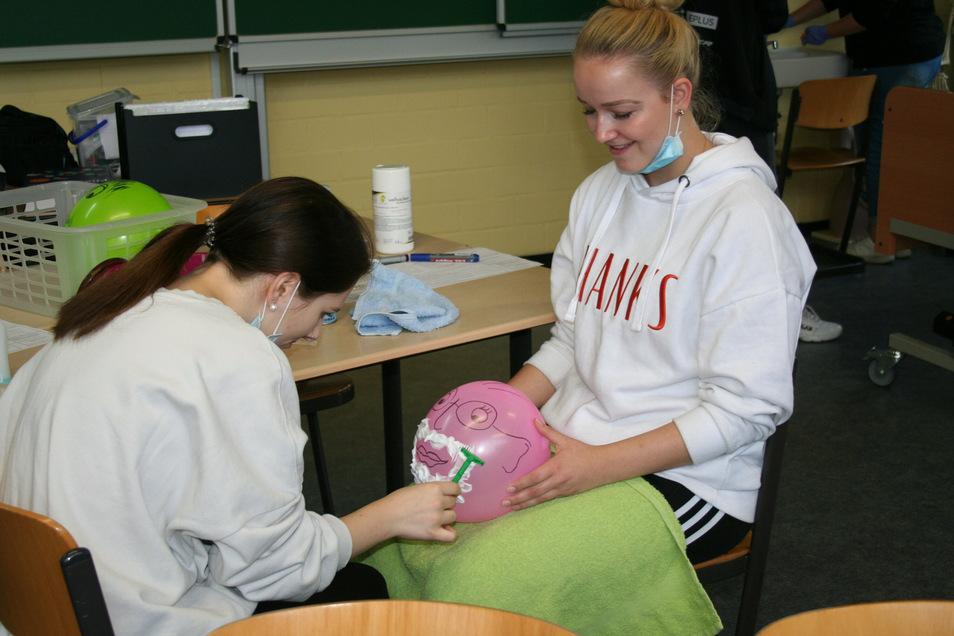 Zur Pflege der Patienten gehört auch die Rasur. Solche Dinge lernen die Pflegefachschüler wie Xenia (l.) und Jennifer im neuen Praxisraum der Großröhrsdorfer Berufsfachschule. Der Luftballon darf nicht platzen, was eine Verletzung bedeuten würde.