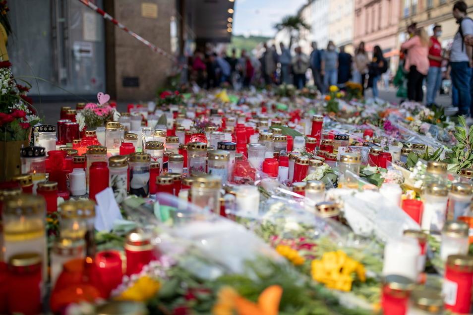 Grablichter, Kerzen und Blumen liegen vor einem Kaufhaus in der Innenstadt, in dem ein Mann am 25. Juni 2021 Menschen mit einem Messer attackiert und getötet hatte. Nun soll der Täter in einer Psychiatrie untergebracht werden.
