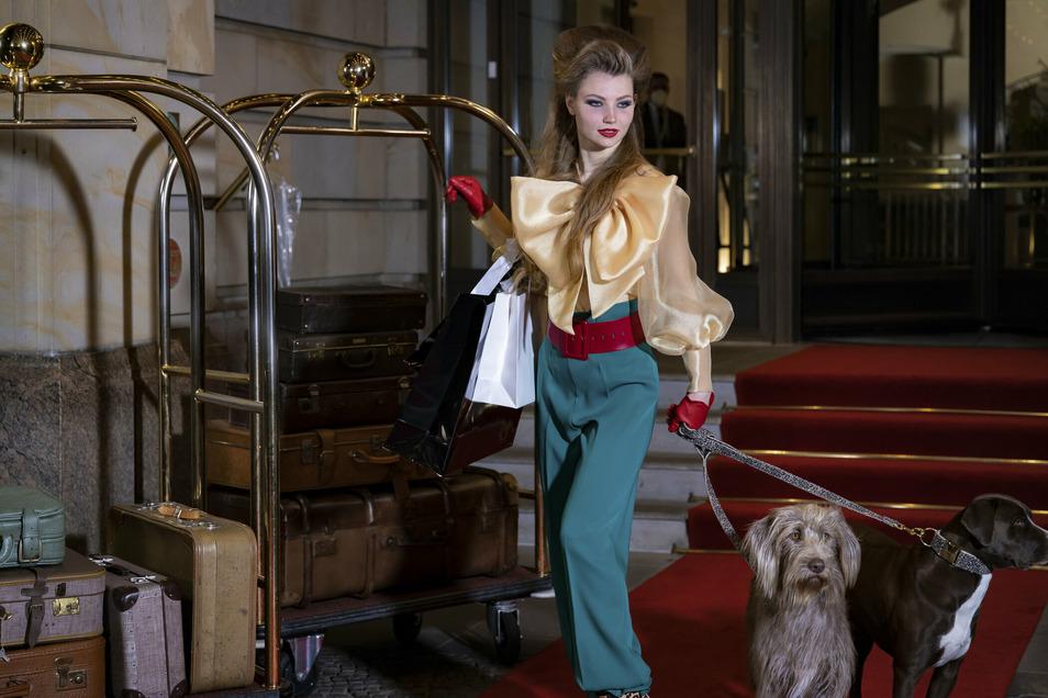 Auf Leo-Print-Rollschuhen und mit zwei großen Hunden an der Leine posiert GNTM-Kandidatin Romy vorm Berliner Adlon-Hotel.