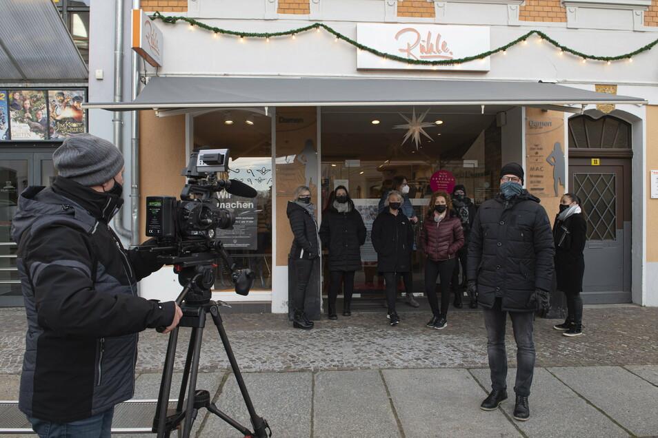 """Das Welt-Fernsehen sendete am Montag live vom Großenhainer Frauenmarkt. Modehändler Ronny Rühle (rechts) nahm an der Aktion """"Wir machen auf-merksam"""" teil, welche die Lage des Handels kritisiert."""