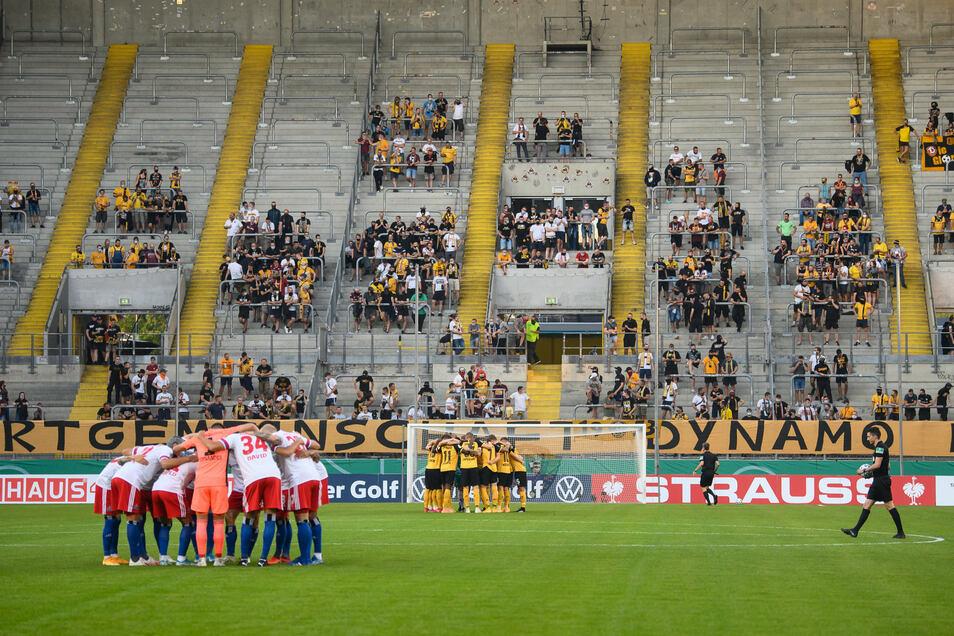 Dynamos und Hamburgs Spieler bilden einen Mannschaftskreis vor dem zwar nur dünn besetzten aber dann sehr lauten K-Block.