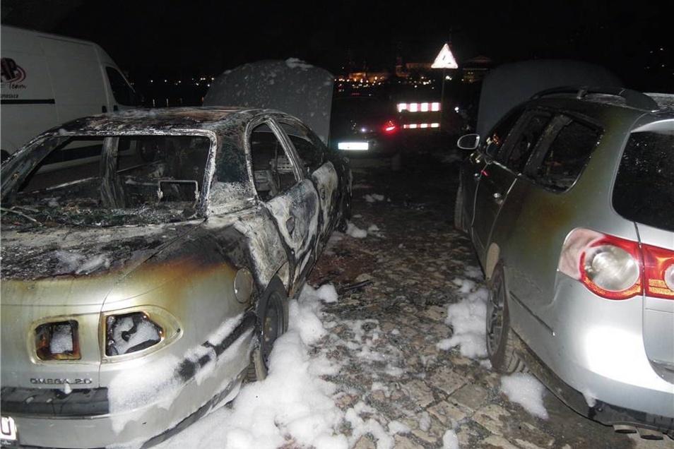 Nur noch Schrott: der ausgebrannte Opel. Schwer angesengt steht rechts daneben der betroffene VW.