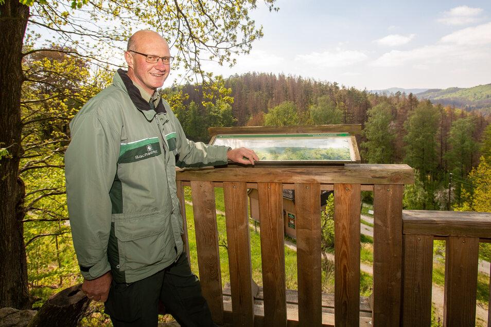 Revierleiter Matthias Protze auf der Aussichtsplattform, dahinter braune Baumspitzen, aber auch frisches Grün.