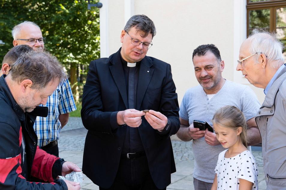 Pfarrer Roland Elsner und der Kirchenrat sind begeistert von der Fülle alter Dokumente und den vielen Münzen.