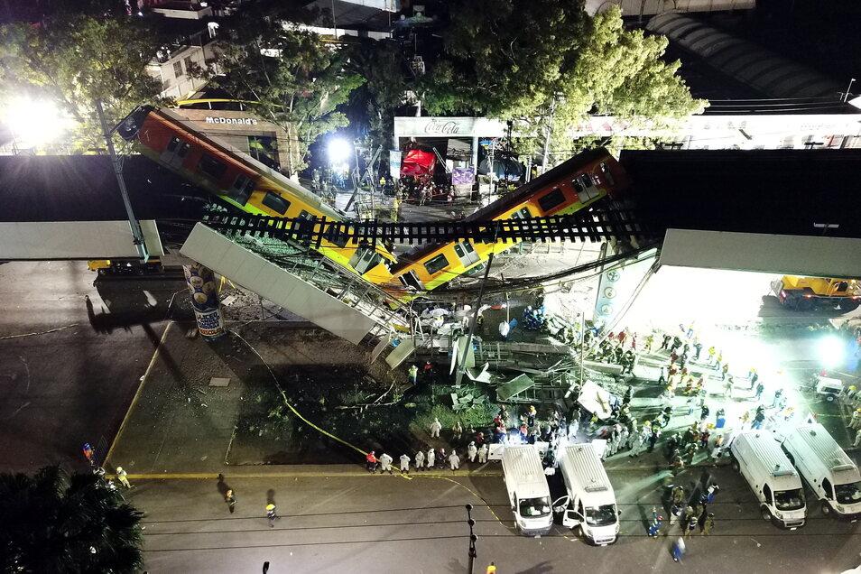 Blick auf den Unfallort vor dem Rettungskräfte stehen nachdem ein Brückenabschnitt der U-Bahn-Linie 12 in Mexiko-Stadt zusammengebrochen ist und mehrere Bahn-Waggons in die Tiefe stürzten.