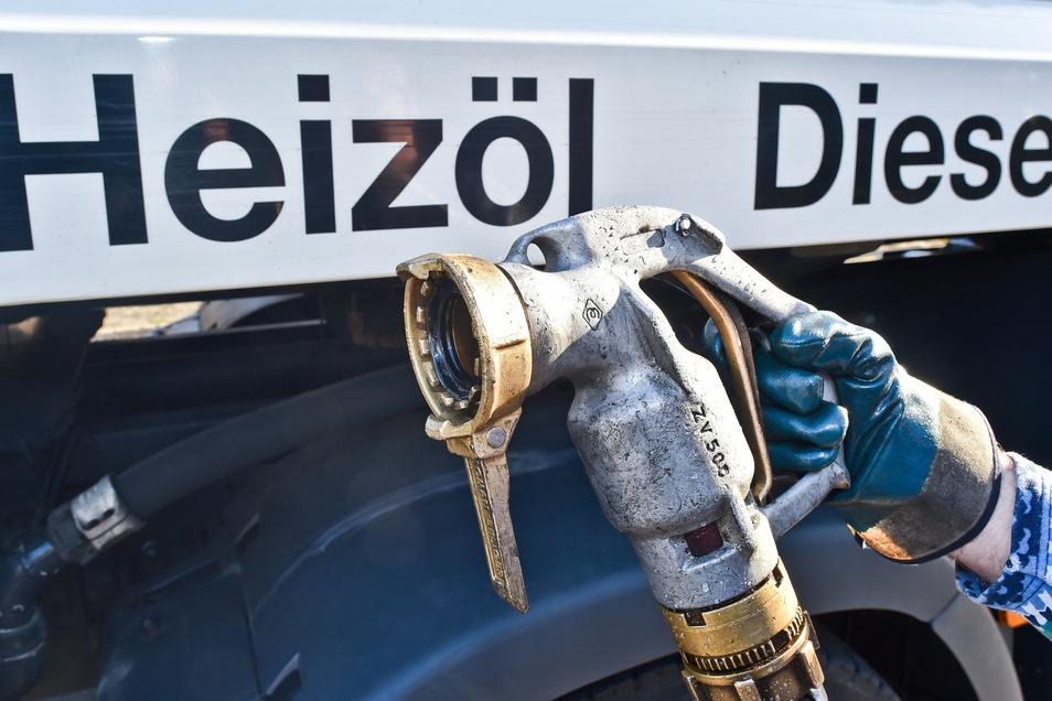 Ein Mitarbeiter eines Heizöllieferanten bereitet die Betankung eines Mehrfamilienhauses mit Heizöl vor.