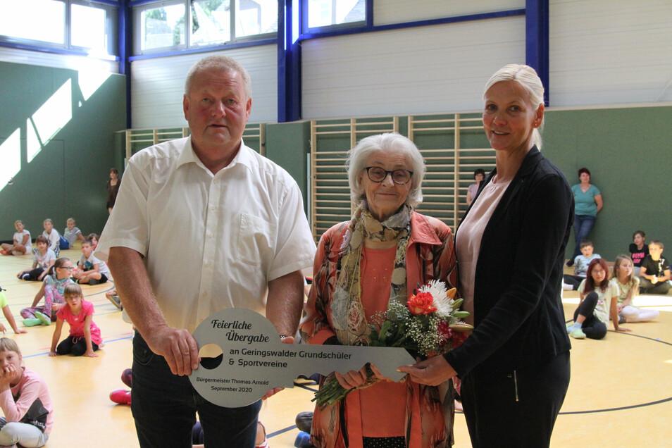 Bürgermeister Thomas Arnold (parteilos) hat den symbolischen Schlüssel an Schulleiterin Silke Simon übergeben. In der Mitte Roselore Sonntag, nach der die Sporthalle benannt ist.