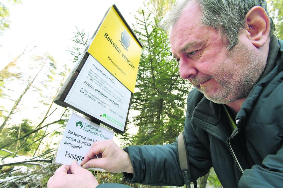 Ab 1. März gelten pauschale Schutzzonen für Brutplätze des Wanderfalken. Für den Uhu gibt es die Ruhezonen jetzt schon ab 1. Februar. Hier pinnt Ulrich Augst ein entsprechendes Schild im Brandtgebiet bei Hohnstein an.