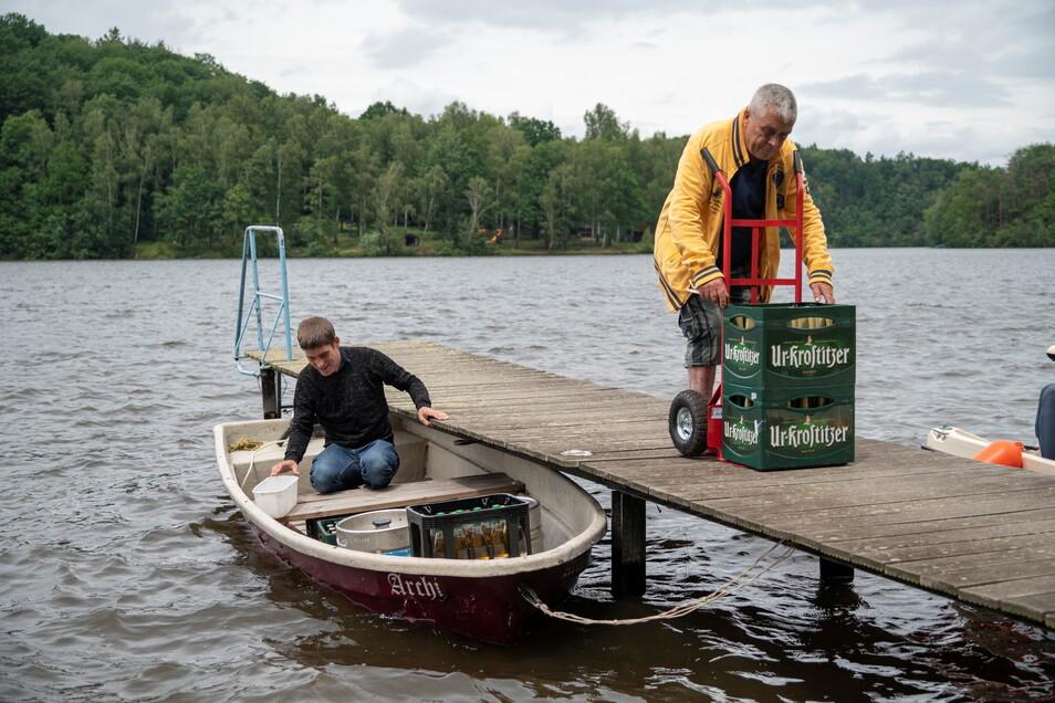 Nach einem Hangrutsch muss die Brunnenquellklause am Kriebsteinsee per Boot beliefert werden. David und Daniel Cox beim Einladen am Bootsanleger.
