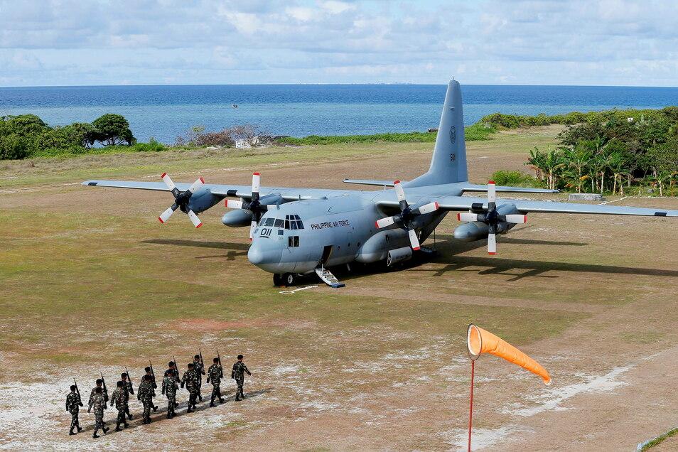 Ein C-130-Transportflugzeug der philippinischen Luftwaffe, während philippinische Truppen auf der von den Philippinen beanspruchten Insel Thitu marschieren.