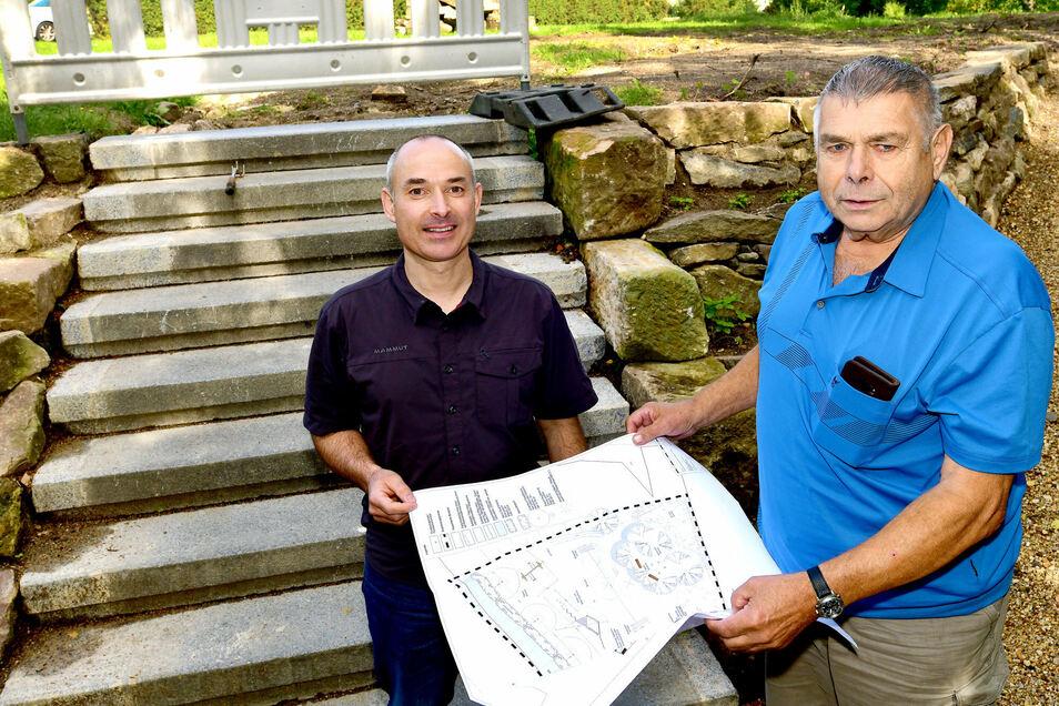 Bürgermeister Günther Ohmann (rechts) und Ralph Berger vom Bauamt der Gemeinde Bertsdorf-Hörnitz mit dem Bauplan für den Mehr-Generationen-Spielplatz in Hörnitz. Die Treppenstufen im Hintergrund stammen von der Bertsdorfer Schule.