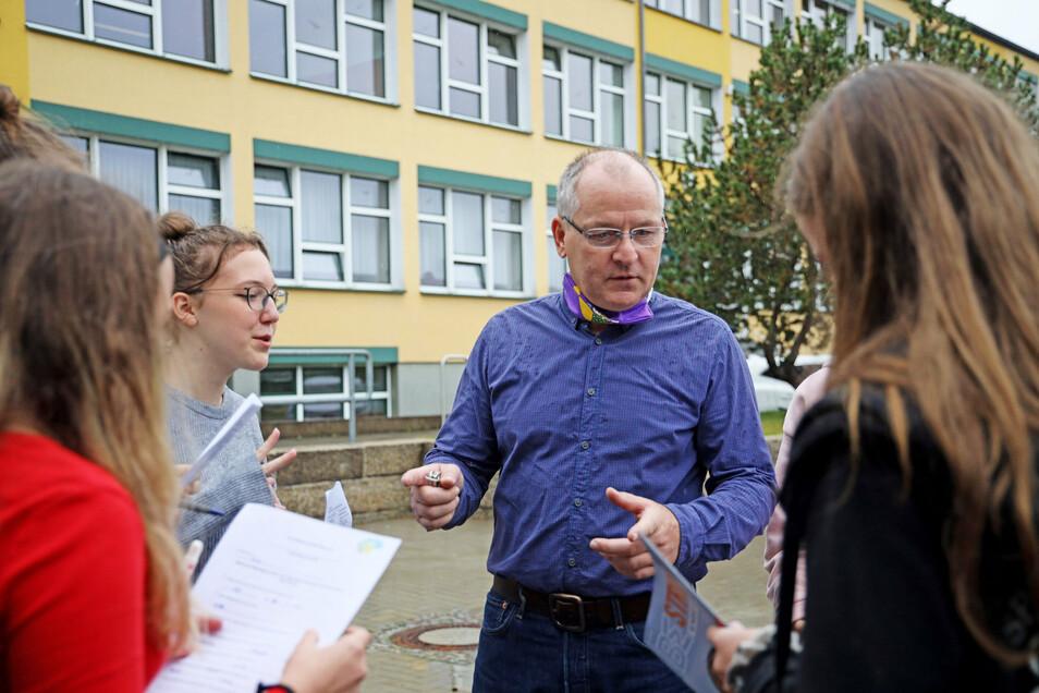 Praxisberater Gerd Wetteborn spricht mit Schülerinnen während der ersten länderübergreifenden Berufsmesse an der Gröditzer Oberschule.