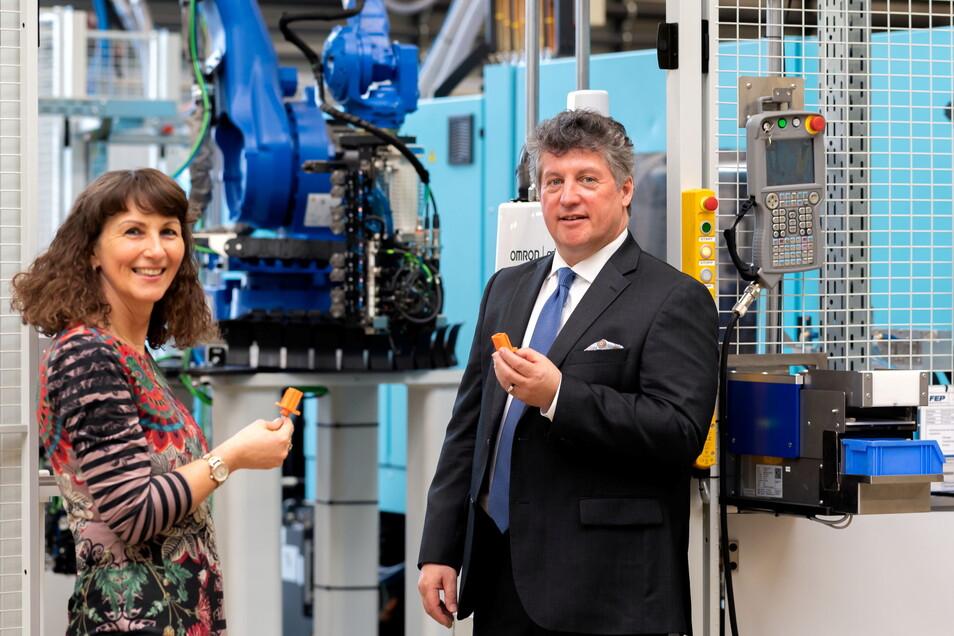 FEP-Geschäftsführer Evelyn Duarte Martinez (l.) und Guido Glinski an der Maschine für die Hochvolt-Stecker: Produkte für die Elektromobilität sind derzeit sehr gefragt.