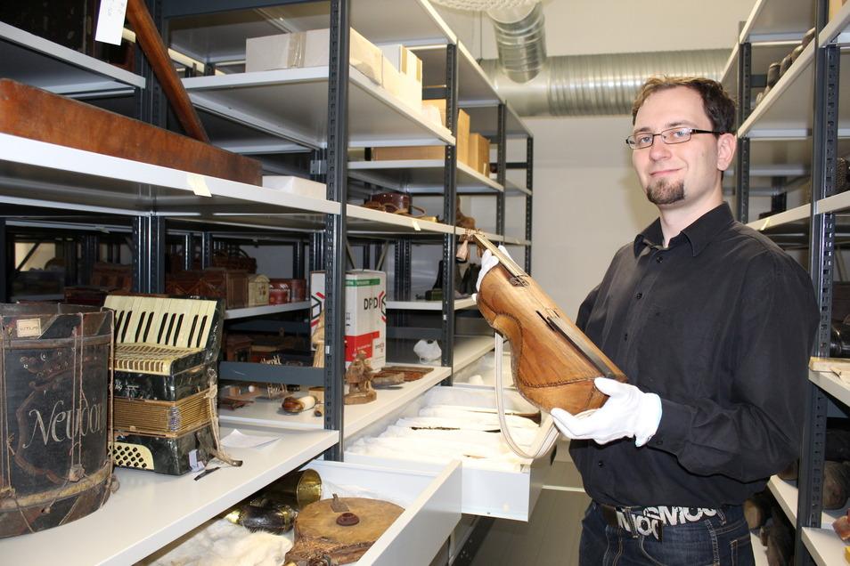 Museologe Alexander Polk zeigt eine historische Geige aus der Instrumentensammlung des Sorbischen Museums in Bautzen. Auch sie hat nun einen neuen Platz im Zentraldepot.