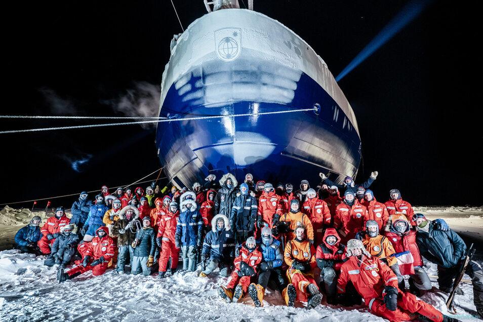 Die derzeitige Mannschaft der Mosaic Forschungsgruppe auf der Polarstern hat sich zu einem Gruppenfoto vor dem Bug vom eingefrorenen Forschungsschiff aufgestellt.