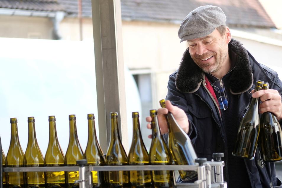 Geschäftsführer Dirk Dobiéy stellt Flaschen auf das Band.