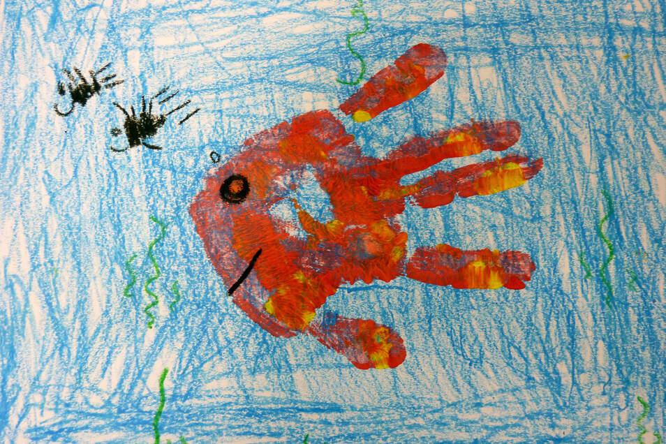 """""""Wie ein Fisch im Wasser"""" hat Finley Magierski sein Bild genannt. Zunächst hat er mit Wachsmalstift den Untergrund, also das Wasser gezeichnet, danach suchte er sich eine helle Farbe aus, mit der eine Handinnenfläche und die Finger angemalt hat. Dann hat"""