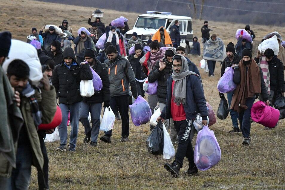 Mit ihren Habseligkeiten gehen die Migranten zurück zum Lager Lipa.