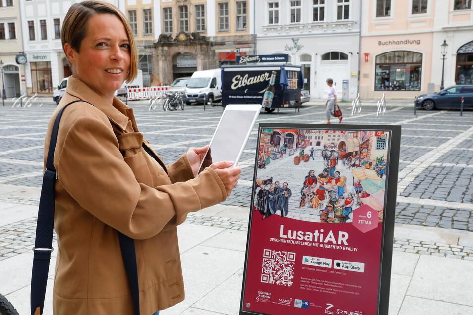 Juliane Wünsche zeigt, wie der Görliwood-Schriftzug auf dem Zittauer Markt erscheint.
