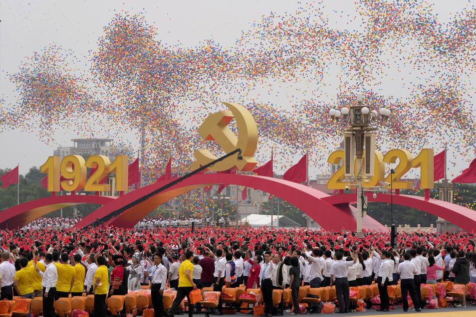 uftballons schweben über Menschen, die an einer Zeremonie auf dem Platz des Himmlischen Friedens anlässlich des 100. Jubiläums der Kommunistischen Partei Chinas chinesische Flaggen schwenken.