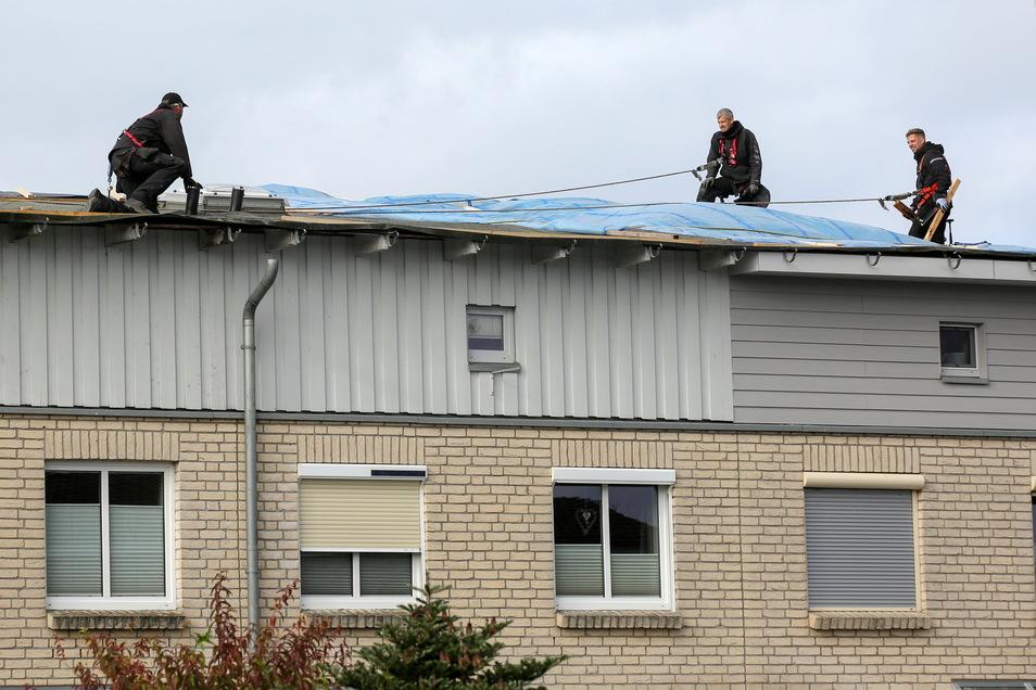 Dachdecker reparieren notdürftig ein Dach von mehreren Wohneinheiten, das durch einen Tornado stark beschädigt wurde.